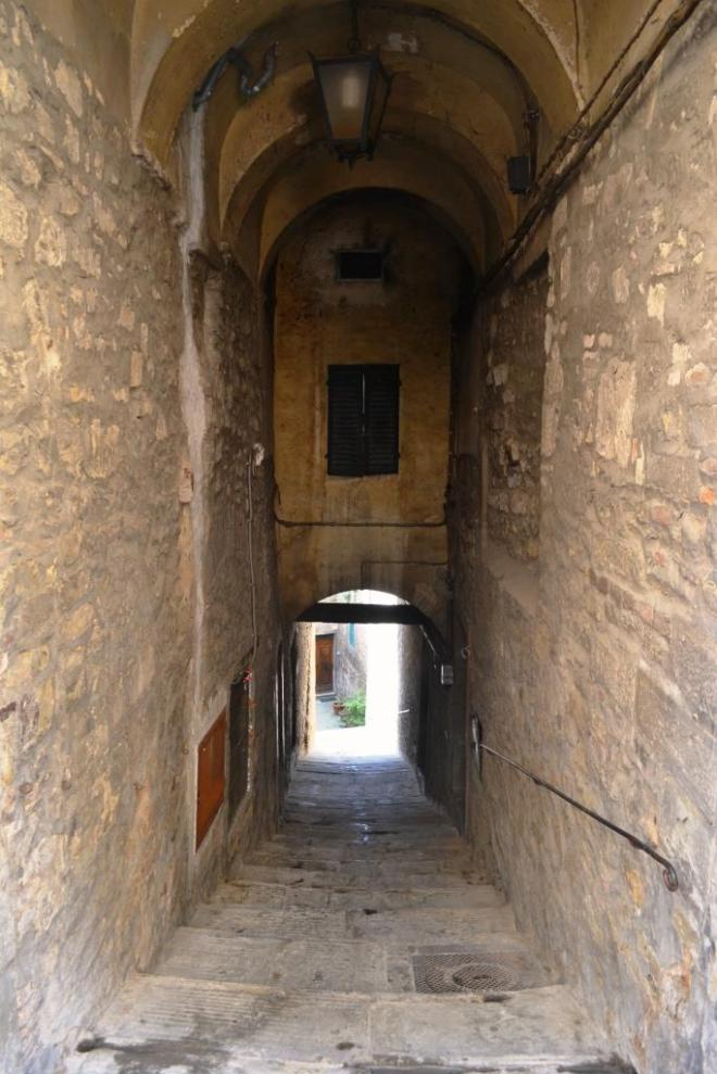 Door at the end of a passageway off Via Nazionale, Cortona, Umbria, Italy