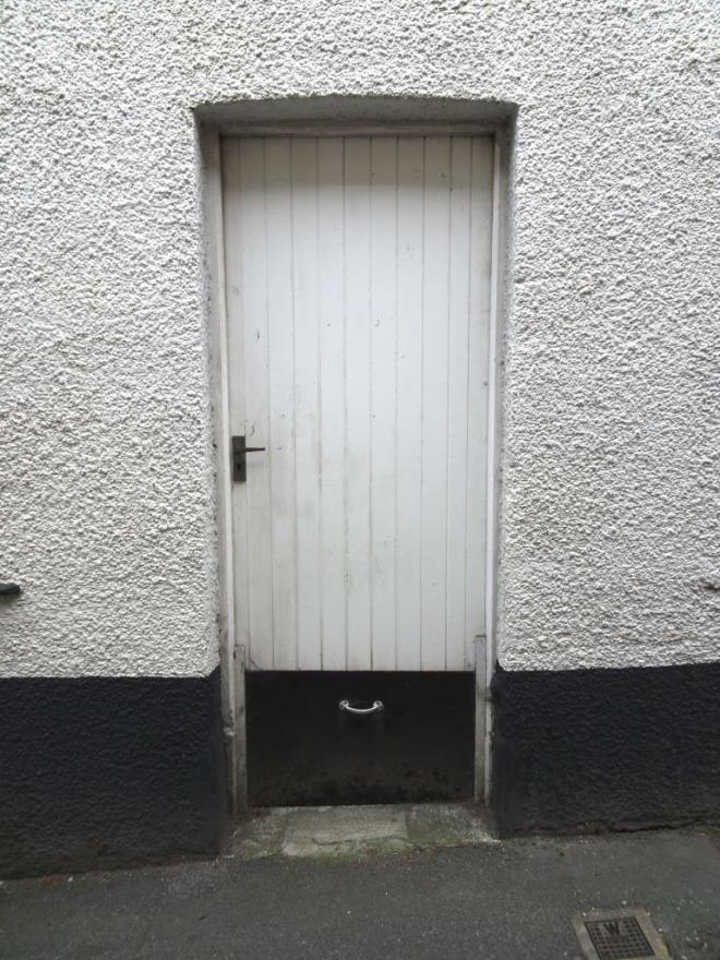 White door with a small black flood gate slotted in at the bottom, Fowey, Cornwall, September 2019