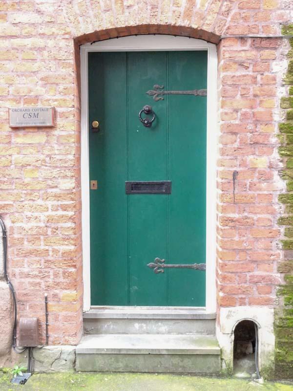Green door with a boot scraper, Bristol, December 2019