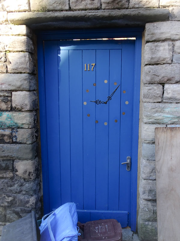 Blue door with a clock painted on it . Six past nine. Bristol, January 2021