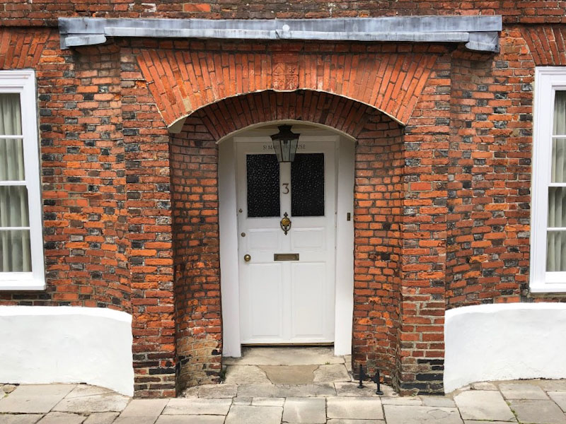 Door with beautiful brickwork including a crest above it, Chichester, May 2021